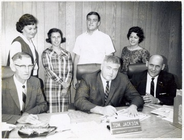 "A photograph of Tom Jackson of the County Court (seated, center), surrounded by Robert Nestor (seated, right) and (standing, left to right): Mrs. Jean Emch, Robin Core, and Harold ""Chip"" Bennett among others."