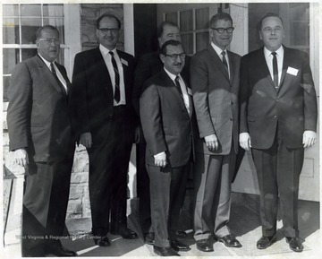 A photograph of Senator Randolph (center, back row) standing outside a building with Secretary of Agriculture Orville Freeman (second from right) and J. W. Ruby (owner of Sterling Faucet) among others.