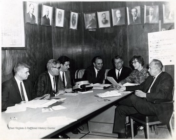 An unidentified group, composed of Mr. Quigley (far right), Mrs. Conn (second from right), Mr. Neilson (fourth from right) and Mr. Sherry (second from left) among others engaged in a meeting.