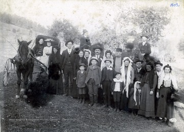 'Charley and Iva Burke Summers in buggy; Sarah Raice, mother of John Wesley Summers wife; John Wesley Summers; Nola Huffman, wife of John Huffman; Phoebe May; John Huffman; Clara Raice, a sister of John Wesley Summers wife; Ira Summers; Fannie Summers; Ernie Simpson; Florence Shahm Nose; Andy Hardsaw; Sadie Pierce; front row: Noren Raice; Harlow Runner; Wade Huffman; J. L. Huffman; Florence Shahm Nose - daughter; Artemis Pierce - on back of horse; Effy Huffman - on horse'