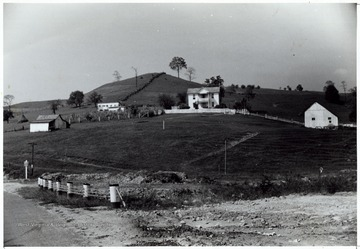 A photograph of an unidentified West Virginia farm with a main house in the center and three buildings surrounding the property. 'Please credit F.S.A; Farm Security Administration'