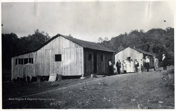 A photograph of a group of people gathered outside an unidentified barn and house.