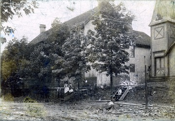 A photograph from the street of two homes, with people sitting on stairs in front.