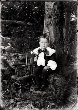 A portrait of Herbert Shock near a chair in Helvetia, W. Va.
