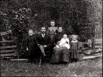 Man and woman and four children pose for portrait outdoors.