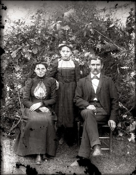 Man, woman, and girl pose for portrait outdoors.