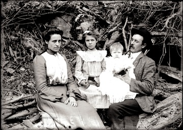 Man and woman with two children seated outdoors for a portrait.