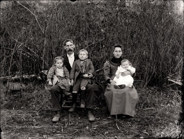 Man, woman, and three children seated outdoors for a portrait.