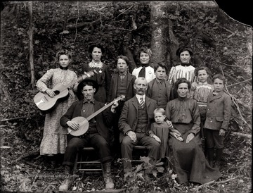 A portrait of a couple with children and extended family members; a male and a female are shown holding a banjo and a guitar.