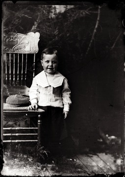 A portrait of smiling boy leaning against a chair taken indoors in Helvetia, W. Va.