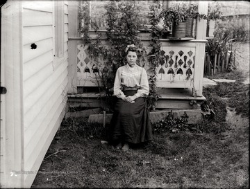 A portrait of seated young woman just outside of the porch in Helvetia, W. Va.