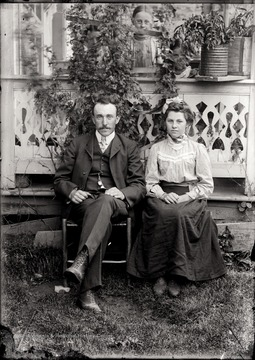 A portrait of seated man and young woman taken outdoor; while they sit their back against the porch, three girls on the porch peek through plants.