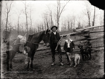 A portrait of man and boy; the father holds a horse rein and a gun; the son holds leashes for three dogs; the photo taken outdoor.