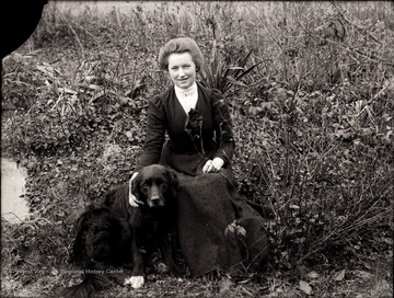 A portrait of woman with her dog by her side.