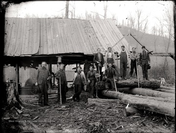 A portrait of loggers with tools in front of lumber mill in Helvetia, W. Va.