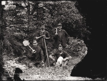 A portrait of four miners with mining tools, taken outdoors.