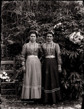 A portrait of two women in the garden near a rhododendron tree.