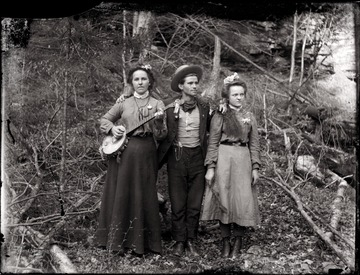 A portrait of a young man and two young women; one of women poses with a banjo.