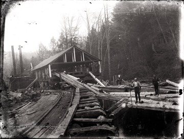 A view of lumber mill, rails leading toward it and loggers on the site, Helvetia, W. Va.