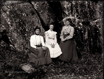 A portrait of three women sitting right at rock ledges.
