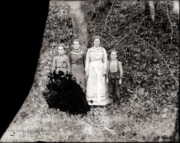 A portrait of three girls and a boy taken outdoors