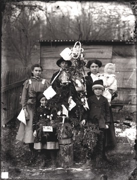 On the left of the tree is Bess Shock and Cinderilla Shock standing in front of her.  Behind the tree is Dan Halderman, a neighbor of the Shock family.  On the right side of the tree is Alma Shock holding baby, Charles R. Shock.  Standing in front of Alma and Charles is brother, Herbert Shock.
