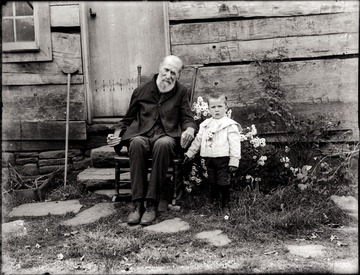 A portrait of seated old man and boy taken just outside of the house in Pickens, W. Va.