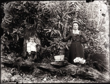 A portrait of woman and boy standing under rhododendron trees.