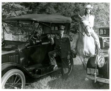 A man in a uniform leans against a 1920 Ford while a woman on horseback poses among several other antique automobiles. Both subjects are not identified.