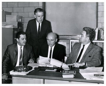 Four men in a room; the center man is identified as John R. McKenzie.
