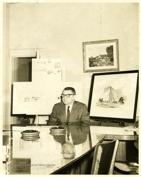 An unidentified male sits in front of architectural drawings.