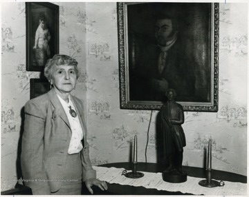 Margaret Barrick stands beside a portrait of her ancestor, Zackquill Morgan and replica of the Patrick Henry statue that use to adorn the top of the Monongalia Court house.