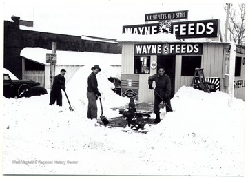 Three men shoveling snow in front of Wayne Feeds on the corner of School Avenue and Hewes Street near Kaiser Fraser Auto shop in Clarksburg.