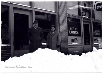 Two men stand on the sidewalk, Hewes Street behind piled snow.