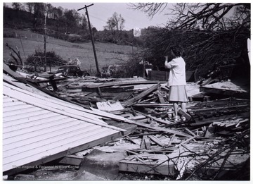 A woman stands on the site after a tornado destroyed a Methodist church, Mount Clare, W. Va.