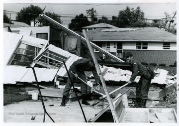 A house destroyed by tornado, near intersection of Smith Street and Pennsylvania Avenue being torn down.