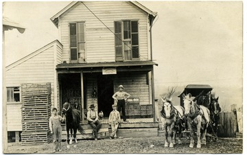 Men, a boy and horses stand around the porch of Geo. W. Minch store.