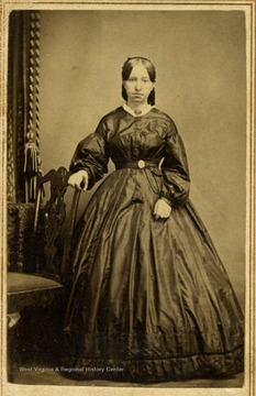 The style of the dress and hair indicates this photograph was taken in the 1860's. The young woman is not identified.