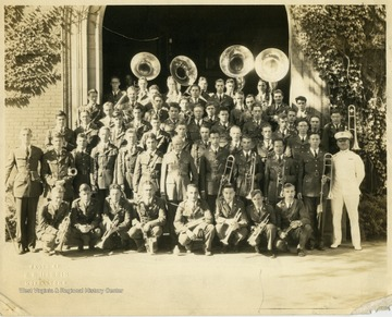 'Left to right, beginning first standing,1. Drum Major, 3. Cal Jacobson, and 6. Paretto Mascioli(?) 2nd row left to right: 10. Samuel Clark(?)14. Walter Mestrezat, Director, and 20. Cal Harry Shelton. 3rd row left to right: Robert Bayles, 24. Junior Macintire, 26. William Broderick, 27. Bernard McGregor and 29. Nathan Hall. 4th row left to right: Wilson Poole Shartidge, and 36. William Barker. 6th row left to right: 49. John Cole, and 50. Walter Cole.'