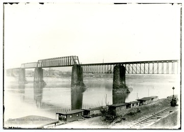 A truss bridge over the Ohio River; people sitting on a railway stretched along the river.