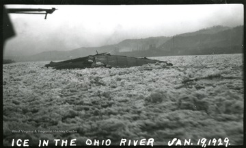 A view of the frozen Ohio River, a river wreck is shown in the midst of the ice.