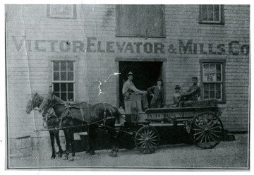 A storefront of Victor Elevator & Mills; men sit in the horse-drawn-store-carriage.