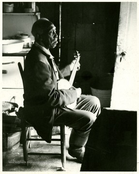 Clarence Tross with a banjo on his laps.