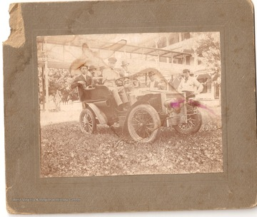"""First car to come to Red Sulphur. The two men standing are J.C. Miller with dark hat on. Bud Dunn with straw hat, Dr. Will Huseter driver of car. Do not know rest. 1906"""