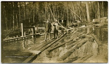"Two men with the long pikes are ""poling"" logs in the log pond toward the jack ladder which takes the logs into the sawmill."
