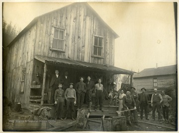 'This picture shows the family group of mostly sawmill men, part of whom lived with Mr. and Mrs. Martin L. Brown in the house shown and includes part of the office force and railroad crew. This group is made up as follows: Left to right: D. D. Brown(standing on the porch), Webb Helmick(standing next to D. D. B.), and Lester H. Sickler(engineer). Standing first on ground: Eugene Schock(sawyer), Charles W. Fenney(stenographer & bookkeeper), Overton(handy-boy from Towanda, Pa.), Eliza Brown(Mrs. M. L. Brown), Fred Brown( with axe, locomotive engineer), W. W. Burton(Boer War, Englishman from England), J. B. White(saw filler), M. L. Brown(mill and yard superintendent) and Sag(setter).'
