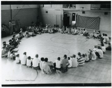 Children seated in a circle in the gym at the Shack.