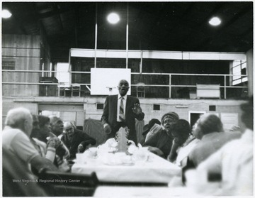 African American man singing at the head of the table.