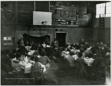 People seated around tables in the gym.