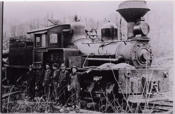 Men posed for a portrait in front of a train.